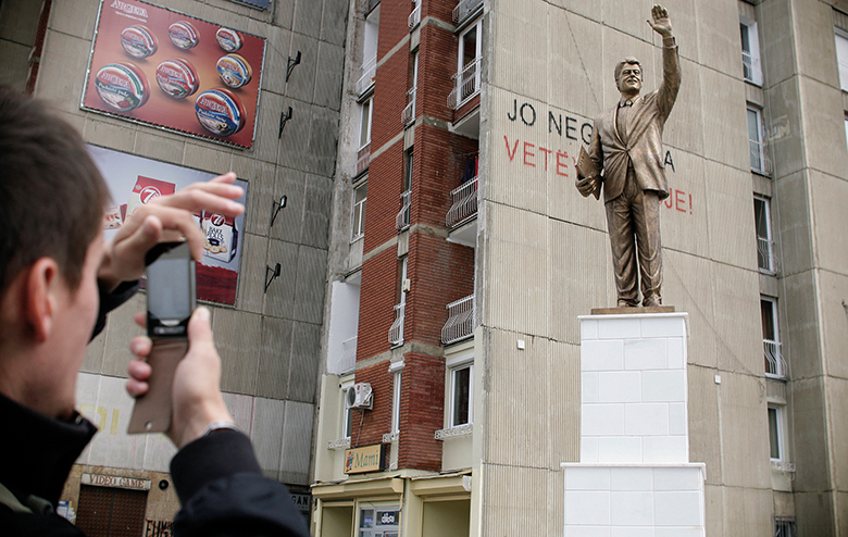 A Kosovo Albanian takes a picture of a monument to former U.S. President Bill Clinton on Bill Clinton Boulevard in Pristina